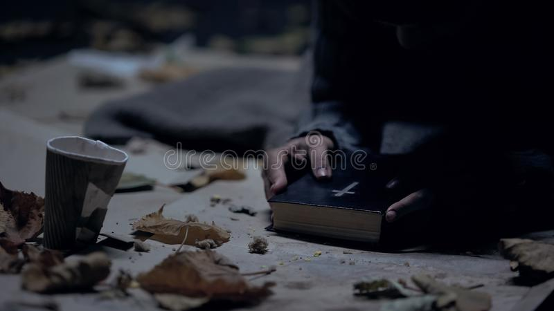 Miserable vagabond holding bible and praying to God, strong belief, faith royalty free stock photography