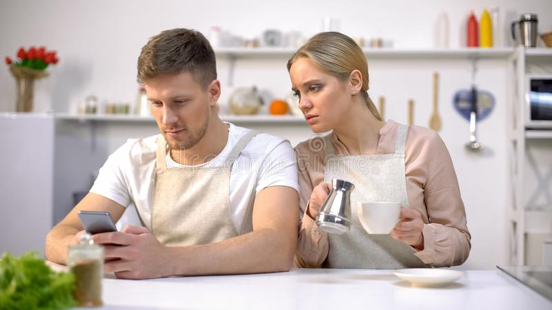 Miserable wife peeping at husband phone, male texting with lover, betrayal. Stock photo royalty free stock photos