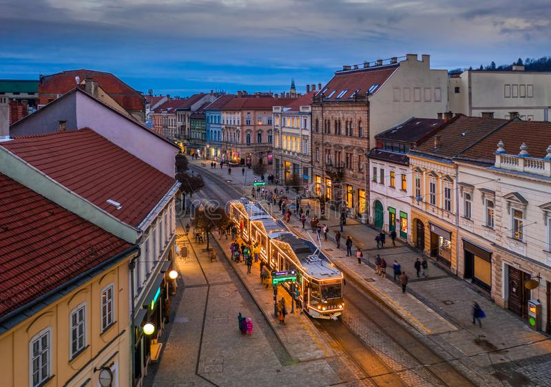 Miskolc, Hungary - Festively decorated Christmas light tram and traditional houses at the high-street of Miskolc, Borsod county. Miskolc, Hungary - Festively royalty free stock photo