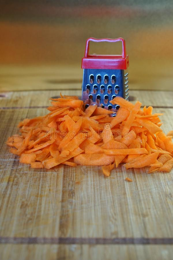 Mismatch: a large carrot next to a small grater. Cutting board on the kitchen table. royalty free stock image