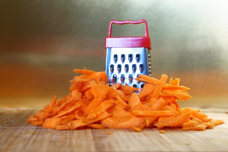 Mismatch: a small grater next to a large carrot. Cutting board on the kitchen table. Unusual mystery and optical illusion. Closeup royalty free stock photo