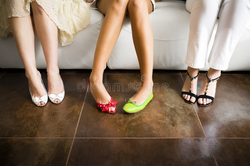 Mismatched shoes. Cropped view of woman wearing mismatched shoes with women in high heels sitting beside stock images