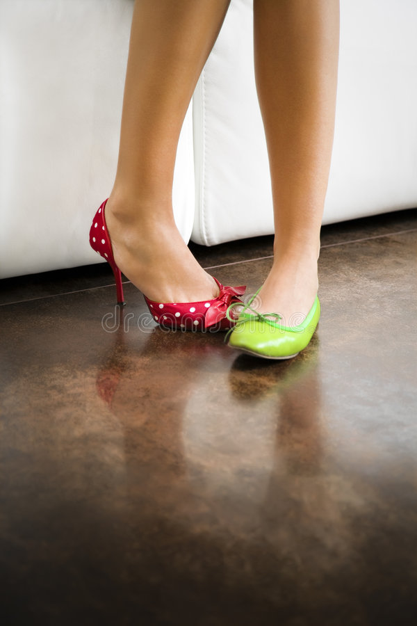 Mismatched shoes. Cropped view of woman wearing mismatched shoes royalty free stock image