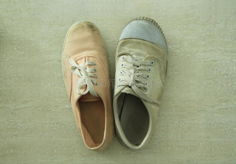 Mismatched white and pink sneakers. On old tiled floor royalty free stock photo