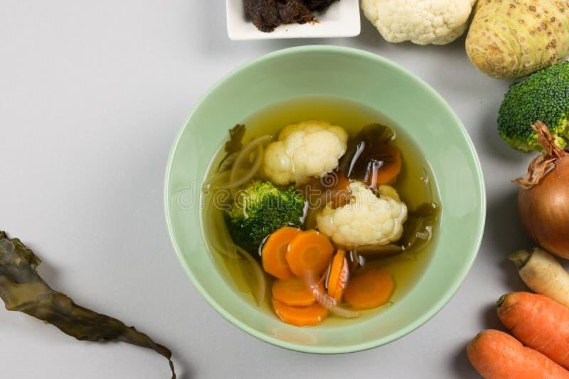 Miso polewka z warzywami gotującymi w naczyniu i świeżymi wokoło go, marchewka, cebula, gałęzatka, brokuły, kalafior na lekkim tl obrazy stock