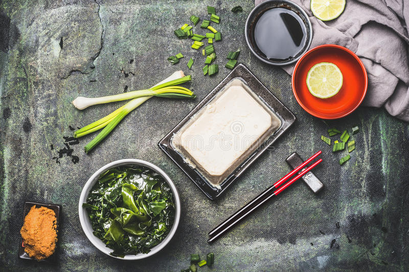 Miso soup cooking ingredients: seaweed, side tofu, miso paste on rustic vintage background, top view. Asian food or Japanese cuisi stock photos