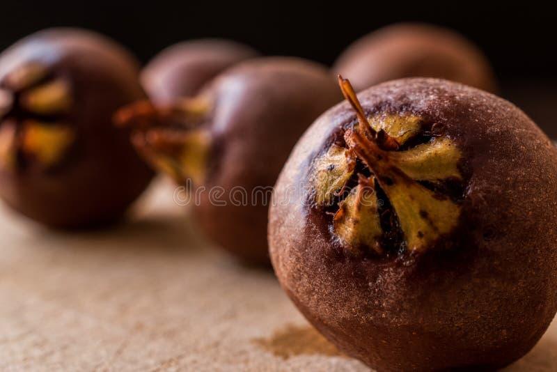 Mispelet bär frukt på en träyttersida royaltyfri bild