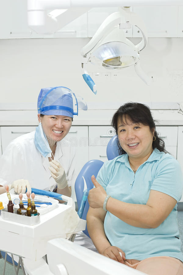 A miss dentist and her patient in clinic royalty free stock photo