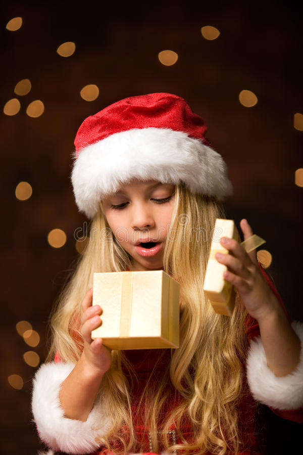 Miss santa. A little christmas girl opens a christmas gift and is surprised royalty free stock images