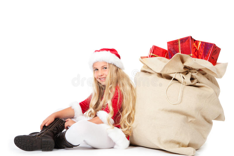 Miss Santa Sitting Beside Christmas Sack Smiling Royalty Free Stock Photography