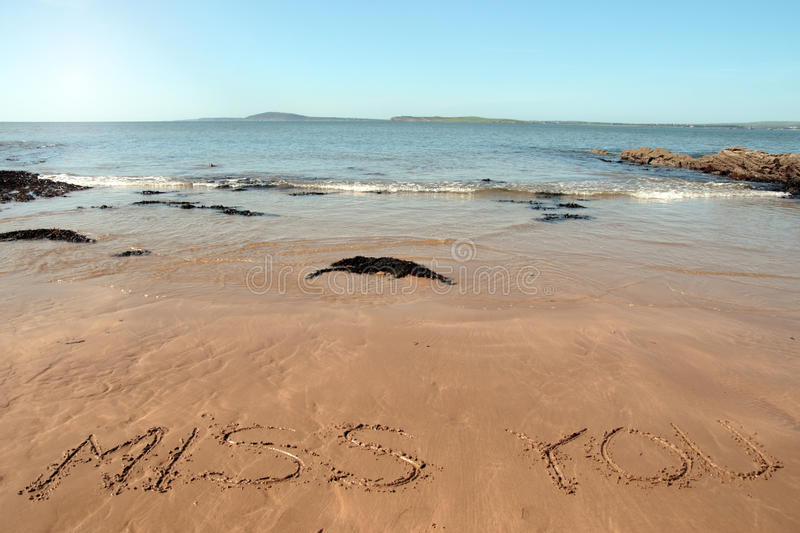 Miss you. Inscribed on the beach with waves in the background on a hot sunny day stock photography