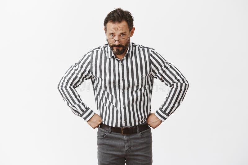 Missachtung wird bestraft Ernst-aussehender strenger Großvater in den Gläsern und in gestreiftem Hemd, Händchenhalten auf Taille stockfoto