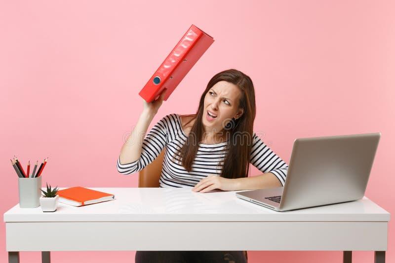 Missbelåten kvinna som döljer bak röd mapp med det pappers- dokumentet som arbetar på projektstund för att sitta på kontoret med  fotografering för bildbyråer