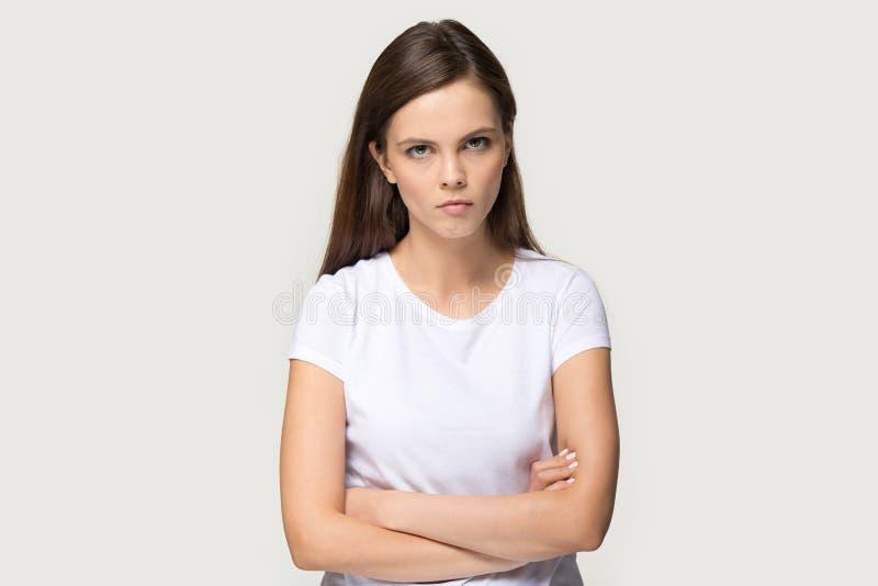 Missbelåten millennial kvinna som ser kameran som poserar på grå bakgrund royaltyfria foton