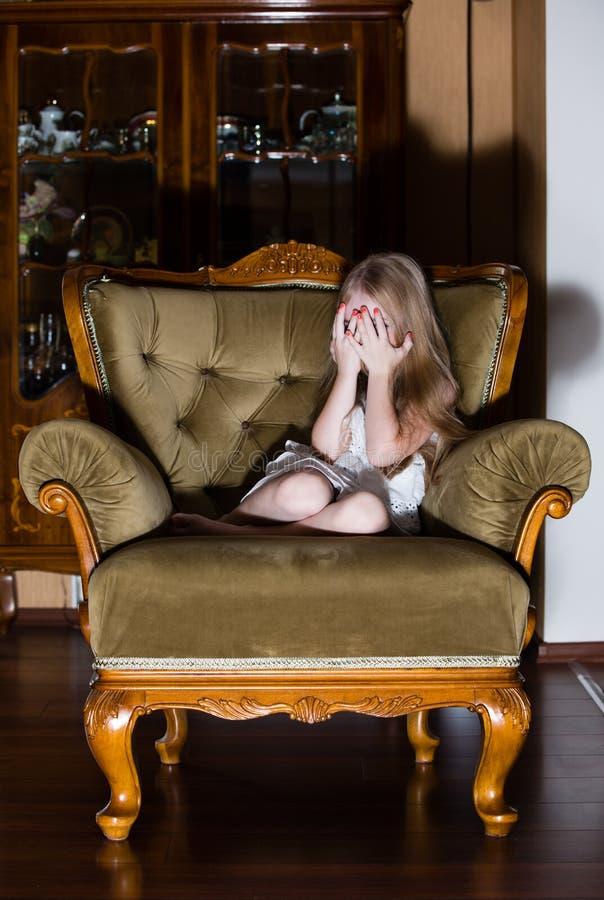 Missbrauchtes kleines Mädchen, das hier Gesicht beim Schreien bedeckt stockbild