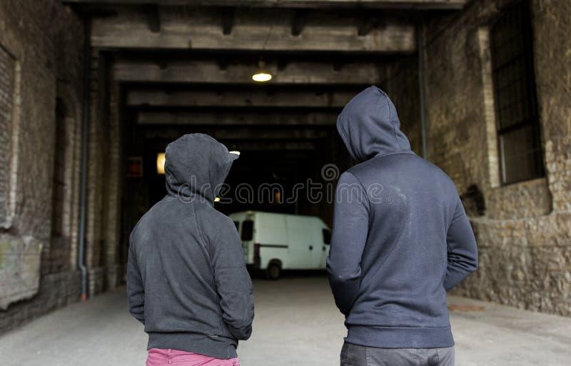 Missbruka män eller brottslingar i hoodies på gatan royaltyfri fotografi