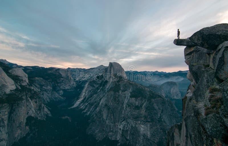 Misschien de beste mening van gletsjerpunt waar deze onbekende avonturier om zich op de rand durft te bevinden stock fotografie