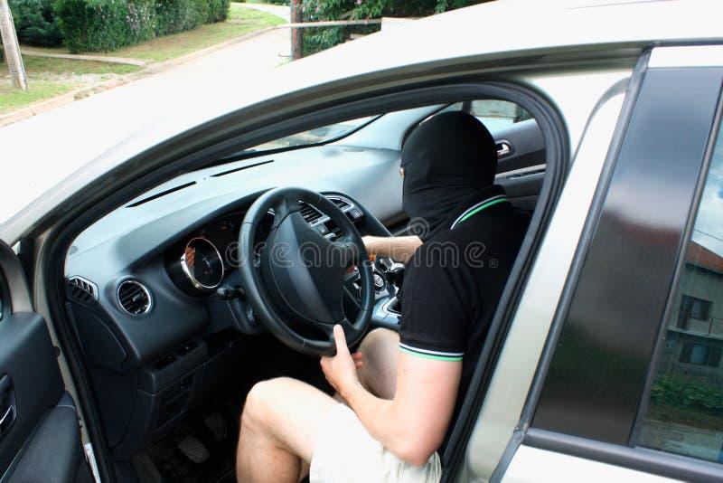 Missdådaren i maskeringen som stjäler bilen fotografering för bildbyråer