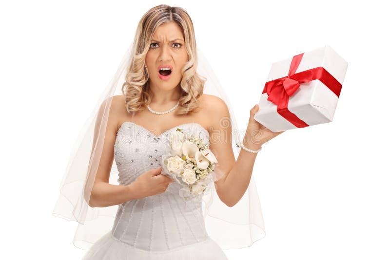 Missfallene Braut, die ein Hochzeitsgeschenk hält lizenzfreies stockfoto
