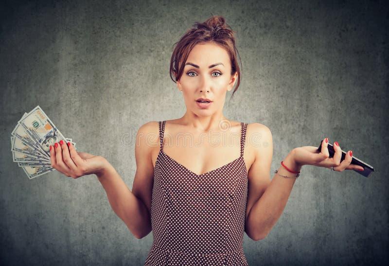 Missfallene Frau, die das intelligente Telefon- und Gelddollarbargeld, unglücklich mit Mobiltelefondienstgebühren hält stockbilder