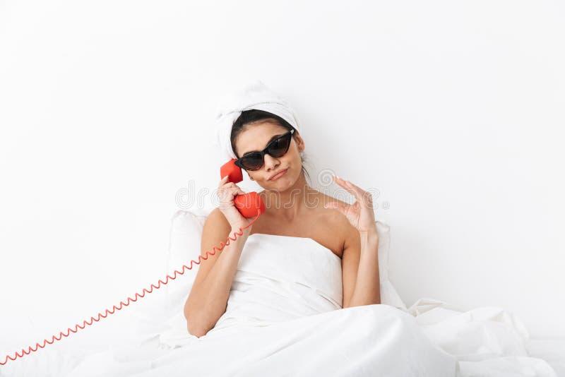 Missfallene Frau mit Tuch auf Hauptl?gen im Bett unter der Decke lokalisiert ?ber tragender Sonnenbrille des wei?en Wandhintergru stockbilder