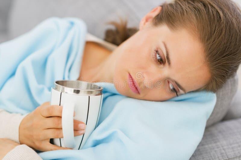 Missfallene junge Frau mit der Grippe, die Schale des Heißgetränks hat stockfotografie