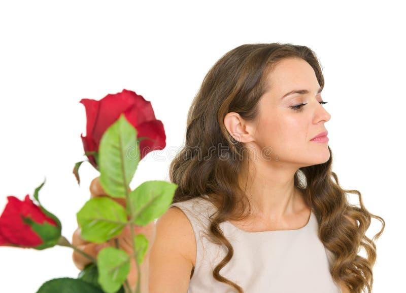 Missfallene junge Frau, die Blumen nimmt stockfotografie