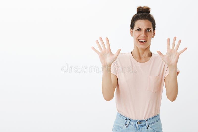 Missfallene ungeschickte und gestörte junge lustige Frau mit dem unordentlichen Brötchen, das Grimasse vom Widerwille- und Abneig stockfotos