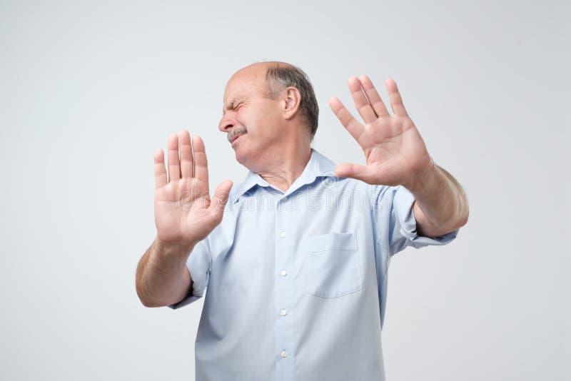Missfallener reifer Mann, der, Hände zur Kamera über grauem Hintergrund ausdehnend ablehnt stockfoto