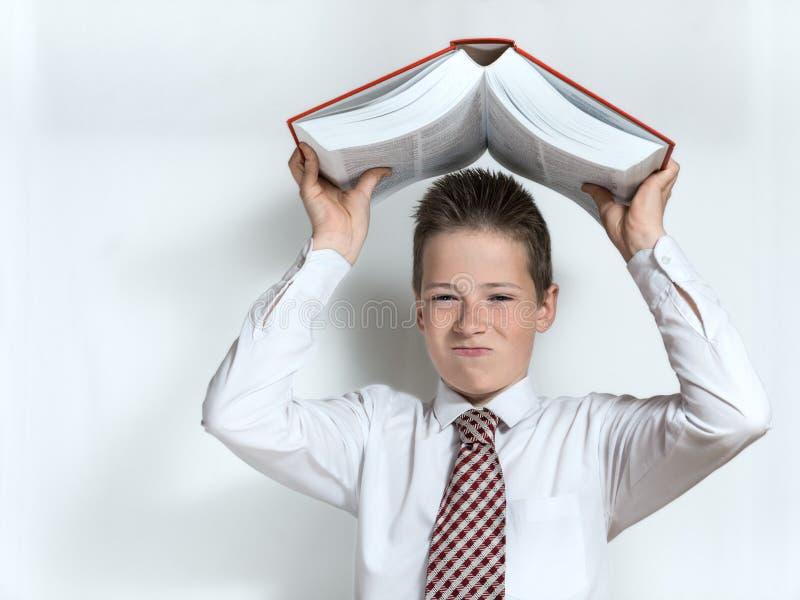 Missfallener Schüler wirft großes Buch stockfotos
