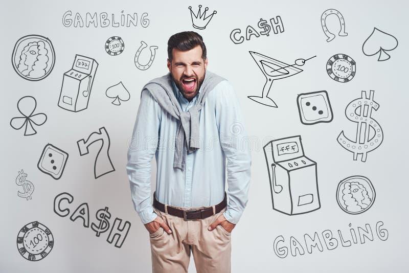 Missgeschick Verärgerter junger Hände in seinen Taschen haltener und bei der Stellung schreiender Mann gegen grauen Hintergrund m lizenzfreies stockfoto