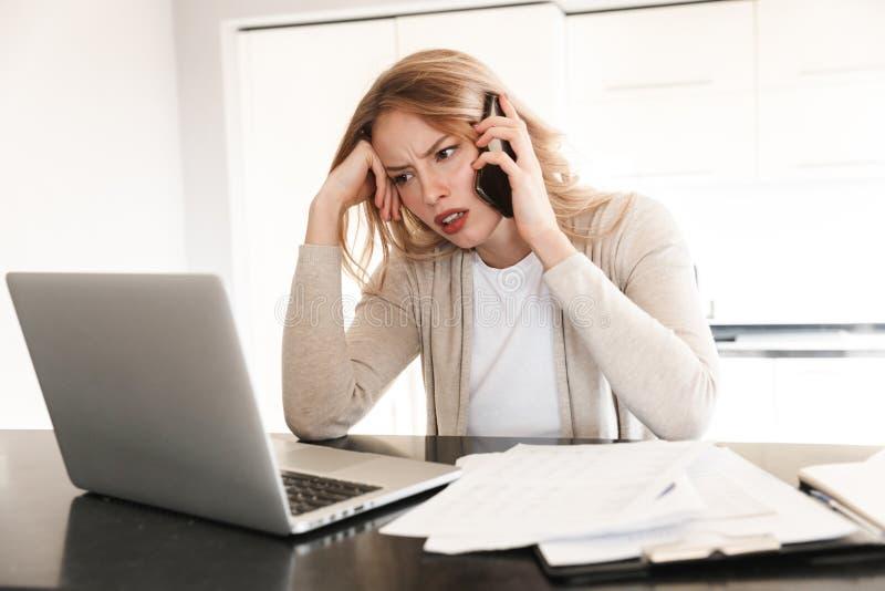 Misshagen blond kvinna som poserar att sitta inomhus hemma genom att använda bärbar datordatoren som talar vid mobiltelefonen royaltyfri foto