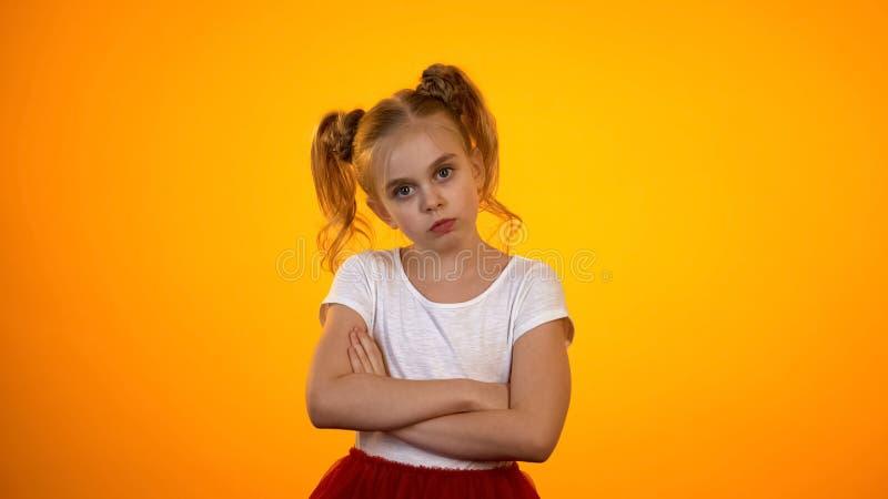 Misshagen flicka med händer som korsas på bröstkorgen som ser till kameran, styggt barn royaltyfri foto