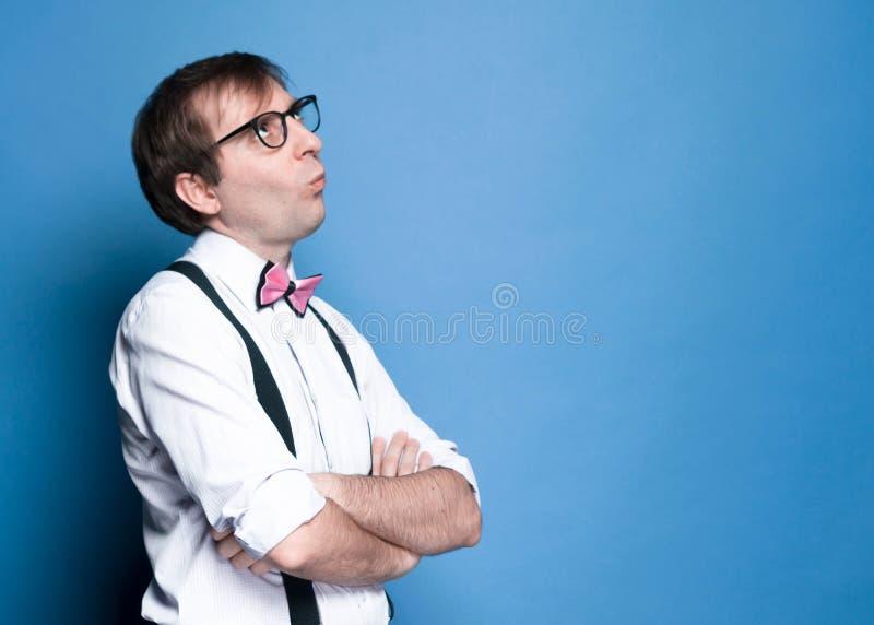 Misshagen slug man med korsade armar i rosa skjorta med hoprullade muffar, flugan, den svarta suspenderen och exponeringsglas som arkivbilder