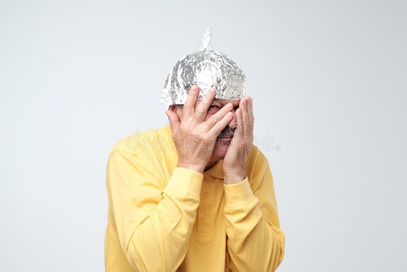 Misshog den mogna mannen för caucasianen i en hatt för tenn- folie att stänga hans framsida med händer royaltyfria bilder