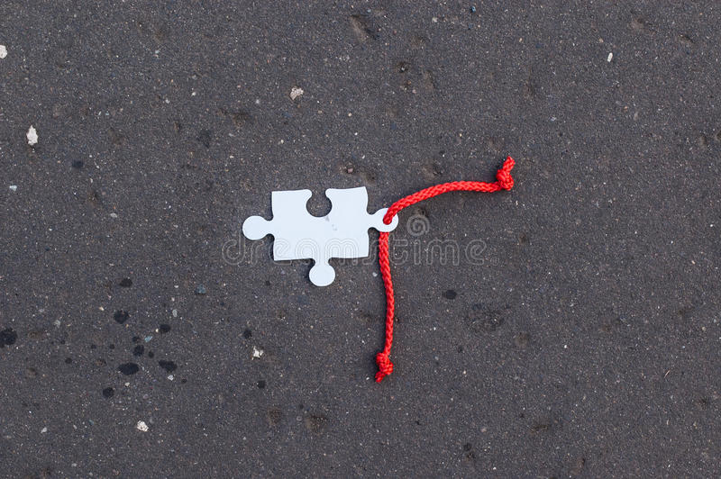 Missing jigsaw piece with red lace laying on tarmac royalty free stock photos