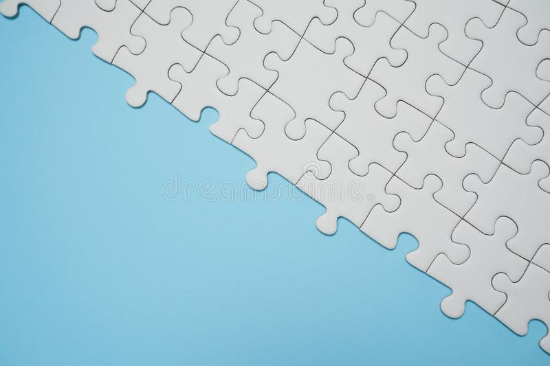 Fragment of a folded white jigsaw puzzle and a pile of uncombed royalty free stock photos