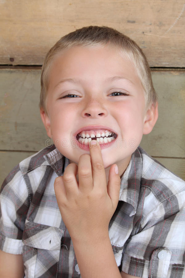 Missing tooth. Cute blond boy showing his missing tooth stock image
