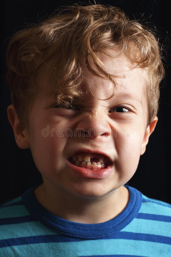 Missing tooth. A closeup of a cute 3 year old toddler with curly blond ringlets missing a tooth. Shallow DOF stock photo