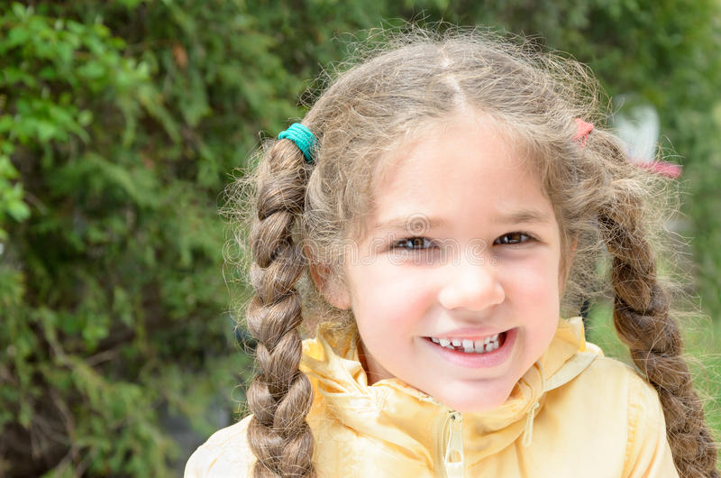 Missing tooth. Cute little girl with missing tooth and long hair braids royalty free stock image