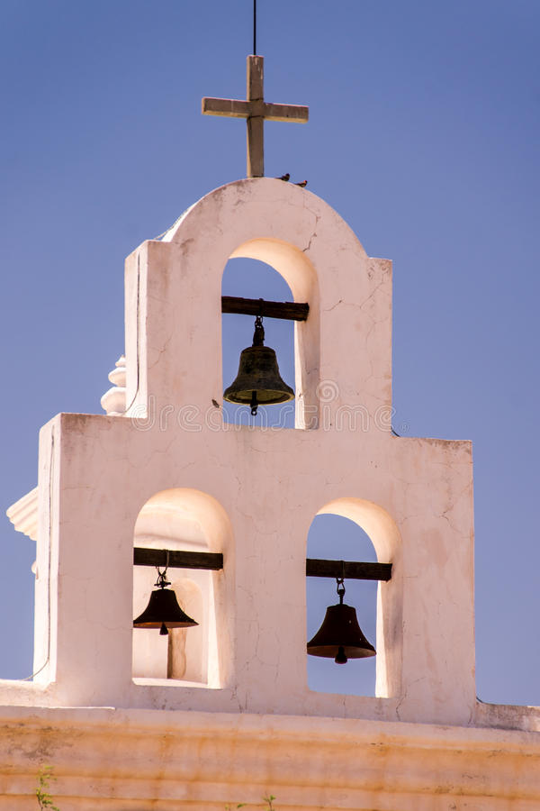 Mission Bells. The bells of San Xavier del Bac mission contrast with blue sky and whitewashed architecture royalty free stock photos