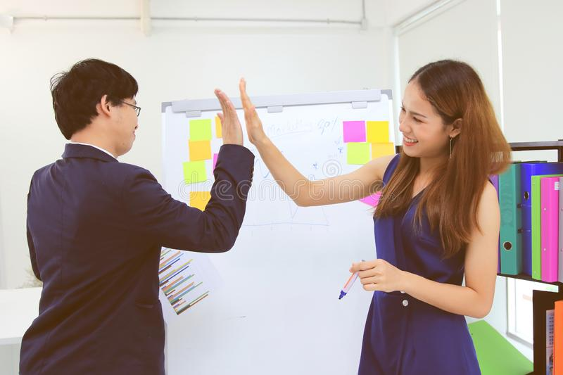 Mission complete. Successful Asian business colleagues giving high five in office stock photography