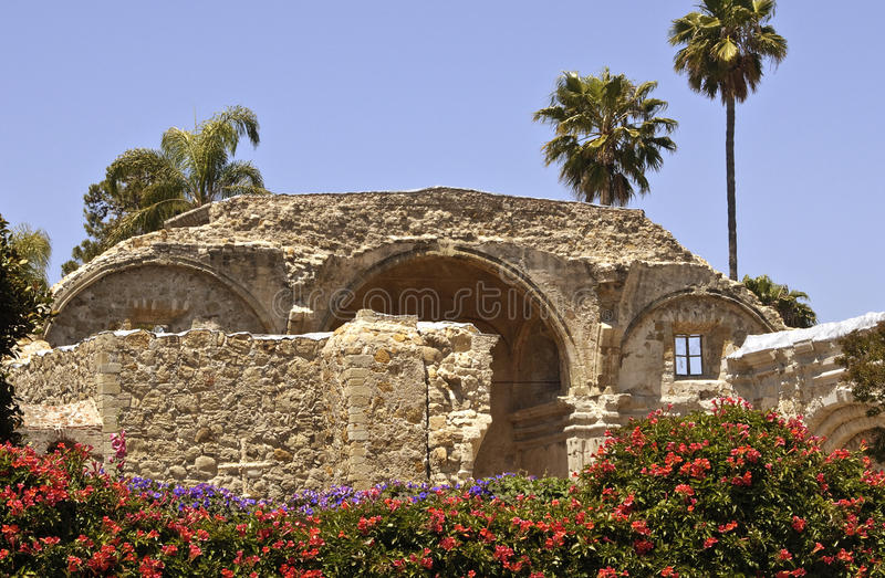 Mission San Juan Capistrano, California. Remains of the old Mission San Juan Capistrano, in Southern California, framed with red and purple flowers and palm stock photo