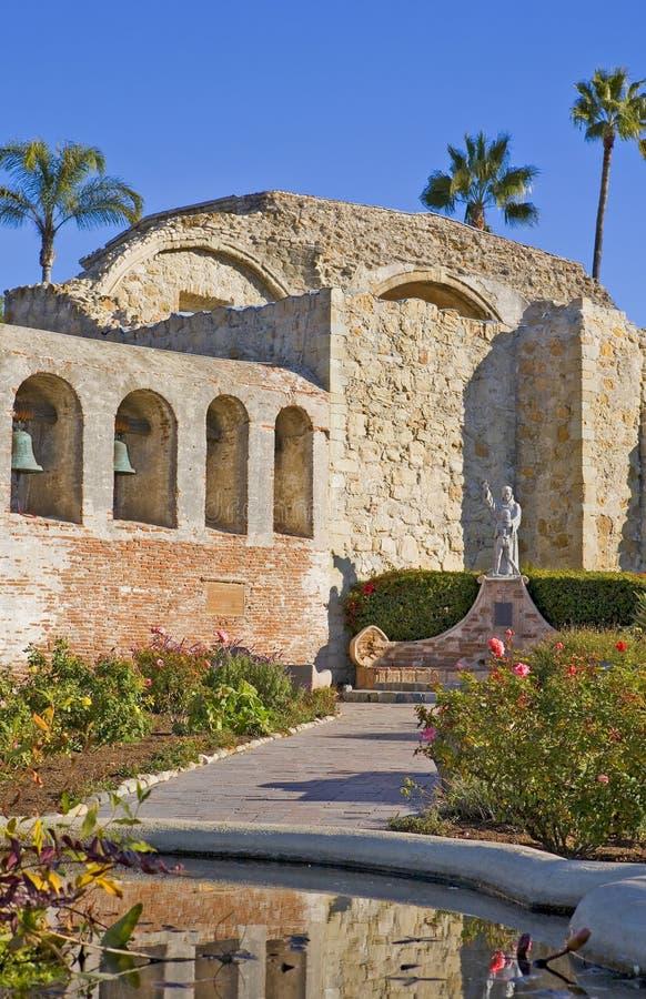 Mission San Juan Capistrano Statue and Bells. Mission San Juan Capistrano with a statue of Father Junipero Serra stock photo