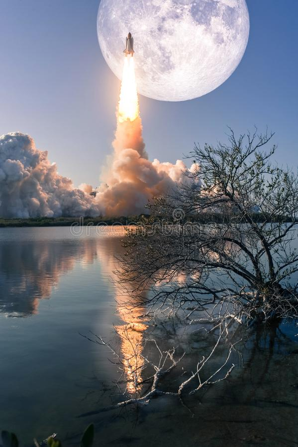 Mission to the Moon, conceptual collage. Space shuttle liftoff is reflected in the water in a swirl of billowing smoke and steam, mission to the Moon, conceptual royalty free stock image