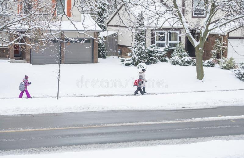Mississauga, Canada - 12 dicembre 2017: Famiglia che cammina alla scuola in tempo di Snowy fotografia stock