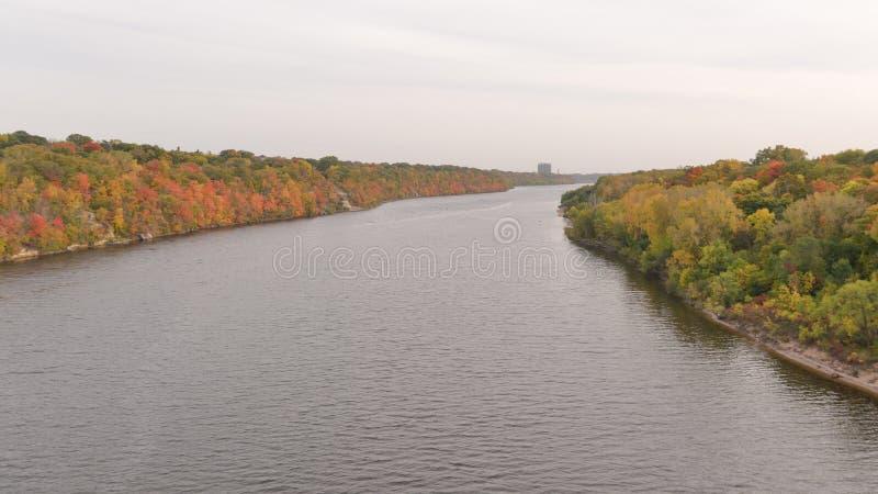 Mississippi River som tas från bron mellan gröna Minneapolis och St Paul - nedgångfärger på träd -, gult, apelsin som är röd royaltyfri bild