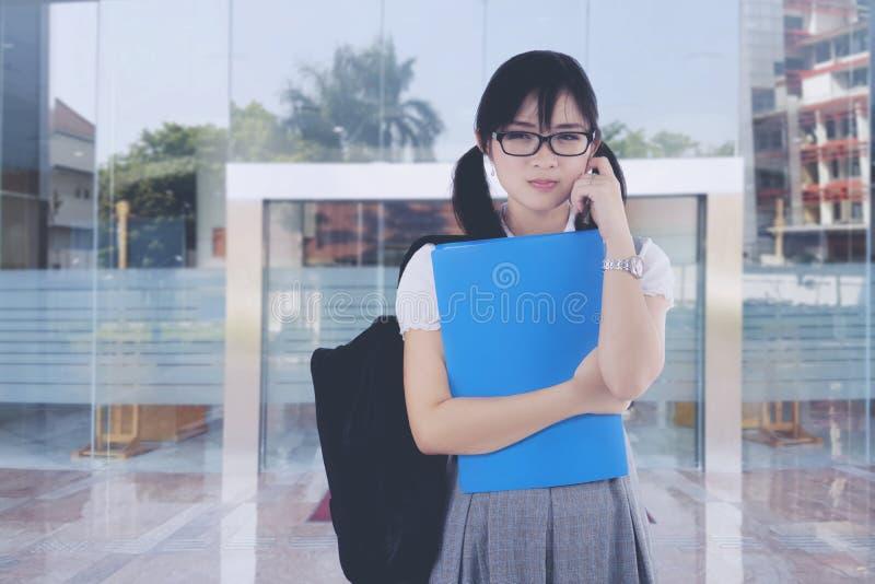 Misslynt asiatisk kvinnlig student framme av universitetet arkivfoto