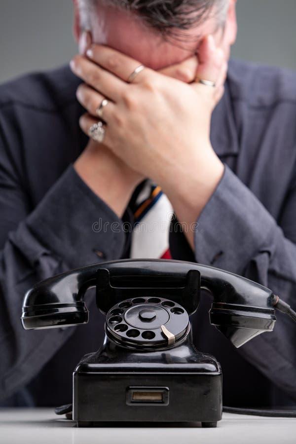 Missmodig man som täcker hans ögon med hans händer royaltyfri bild