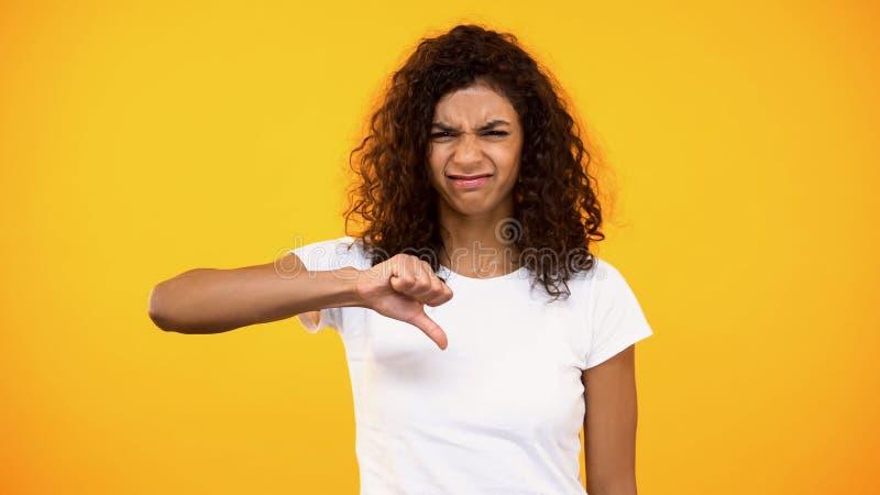 Missnöjd afro--amerikan kvinnliga visande tummar ner, olyckligt med dålig service arkivfoton